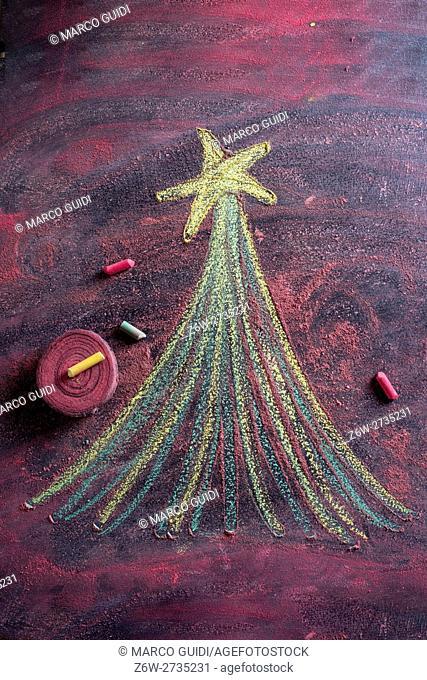 Small stylized christmas tree on blackboard with chalk