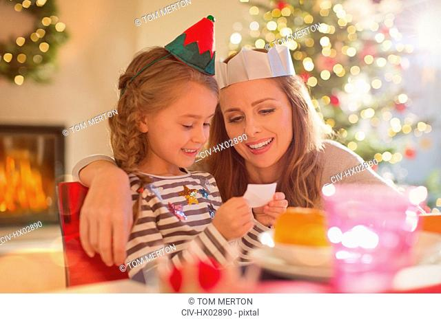 Mother and daughter wearing paper crowns at Christmas dinner table