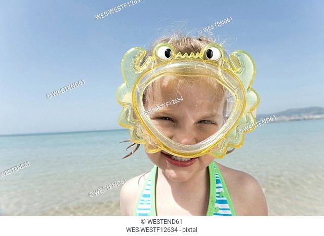 Spain, Mallorca, Girl 4-5 on the beach wearing diving goggles, portrait