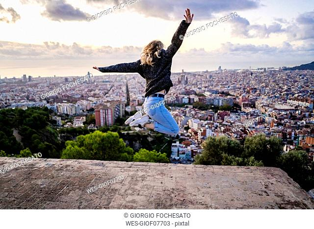 Carefree young woman jumping above the city at sunrise, Barcelona, Spain