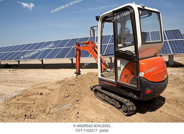 Mechanical digger on solar panel construction site