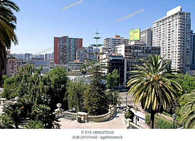 Highrise modern apartment blocks in downtown from the Cerro Santa Lucia with sweeping classical balustrade and Chilean Palm tree in the foreground