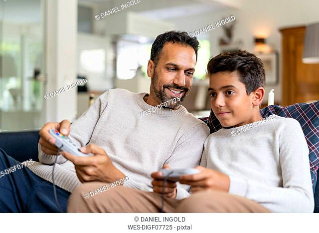 Happy father and son playing video game on couch in living room