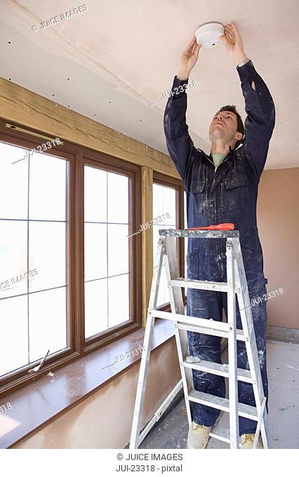 Man on ladder installing smoke detector
