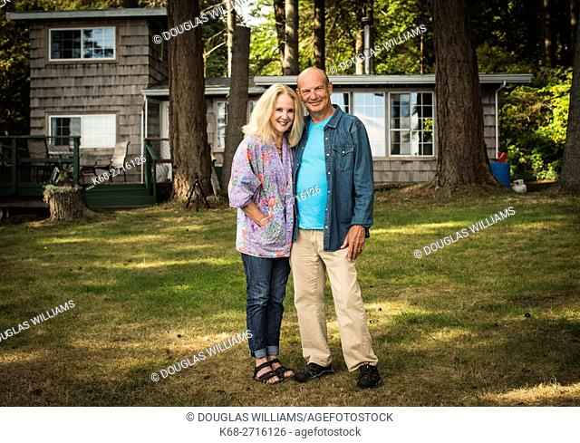 A couple in their 60s pose in front of a sea side cabin in Point Roberts, Washington state, USA