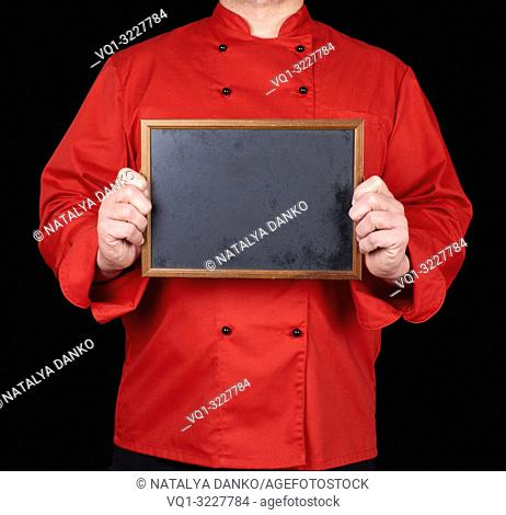 chef in red uniform holding an empty wooden frame with black background