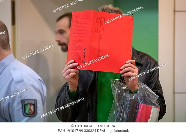 17 October 2019, North Rhine-Westphalia, Bielefeld: A defendant holds a loose-leaf binder in front of his face as he enters a courtroom in the district court...