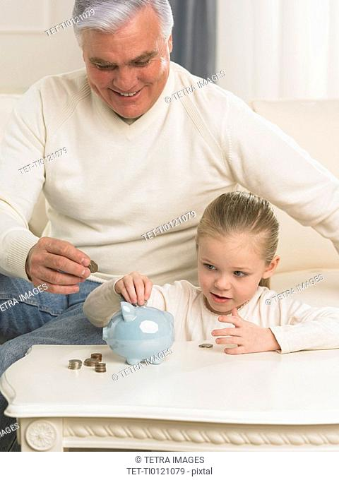 Grandfather and young granddaughter putting change in piggy bank