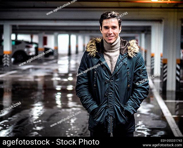 Young trendy man in winter outerwear standing in car parking and smiling to the camera