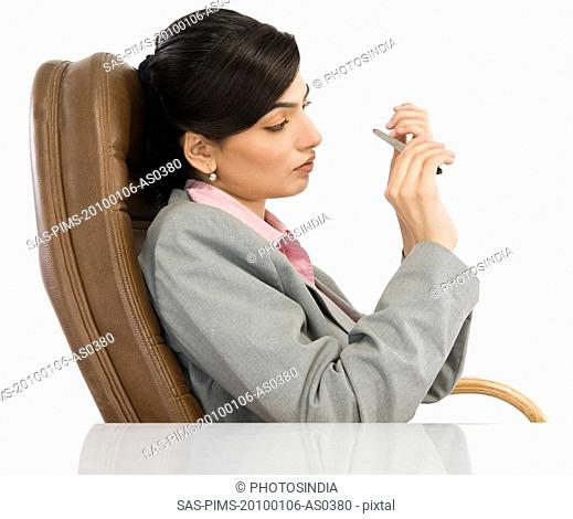 Businesswoman filing her nails in an office
