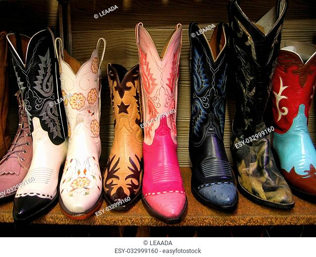 A row of colorful cowboy boots on a shelf