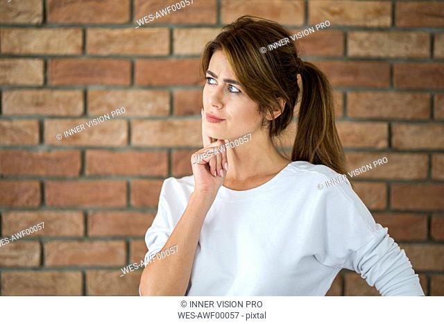 Portrait of thinking young woman in front of brick wall