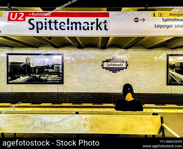 Berlin, Germany. Young adult caucasian girl fully concentrated towards her smartphone while waiting for her connecting U-Bahn Commuter Train