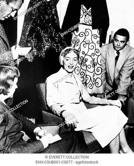 Christine Jorgensen, displays her night club act wardrobe at a press conference. She expressed discomfort at 'being turned into a joke