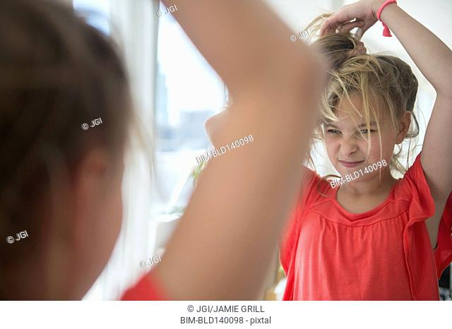 Caucasian girl playing with her hair at mirror