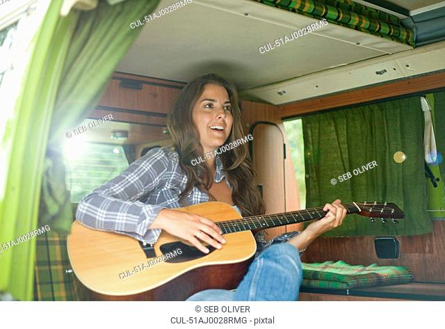 Woman playing guitar in trailer