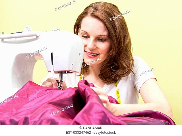 Brunette european woman sewing diy at home in front of yoellow background