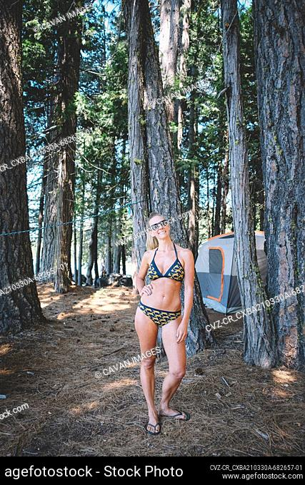 Woman with Cheetah Bikini Poses for a photo While camping