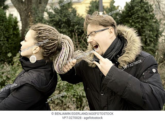 man using hair of woman as microphone, screaming loud his opinion, multiracial couple, in Cottbus, Brandenburg, Germany
