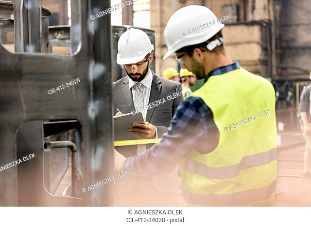 Manager with clipboard and steel worker with tape measure in factory