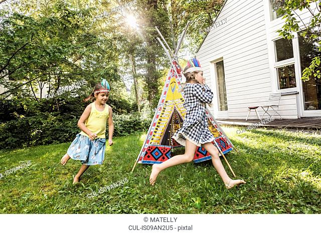 Two girls in native American headdress running around teepee in garden