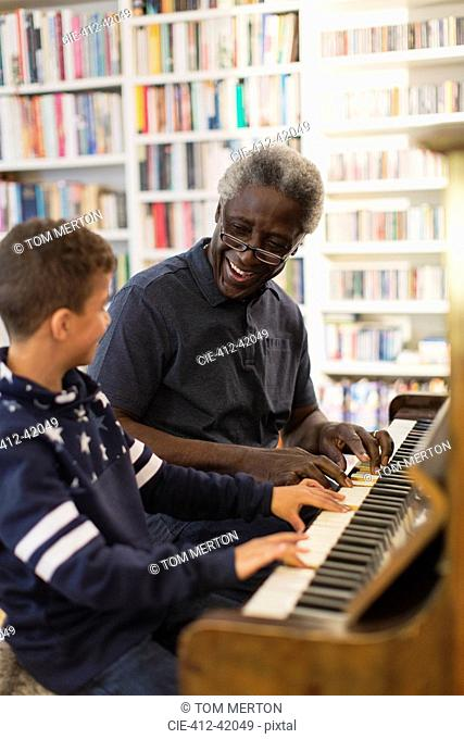 Grandfather and grandson playing piano