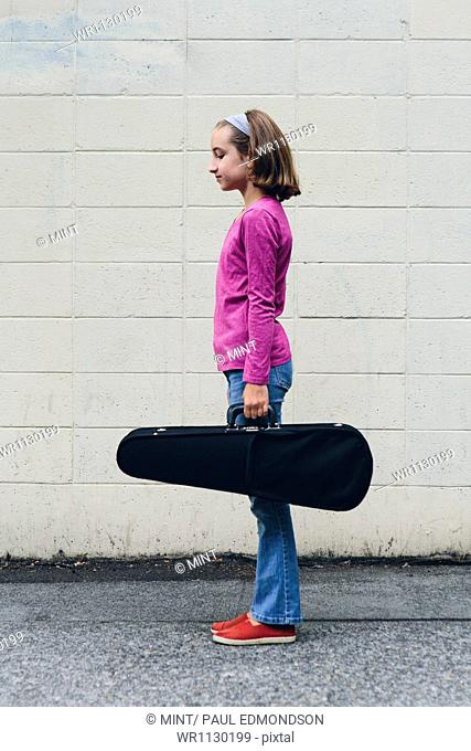A ten year old girl carrying a violin in a case on an urban street