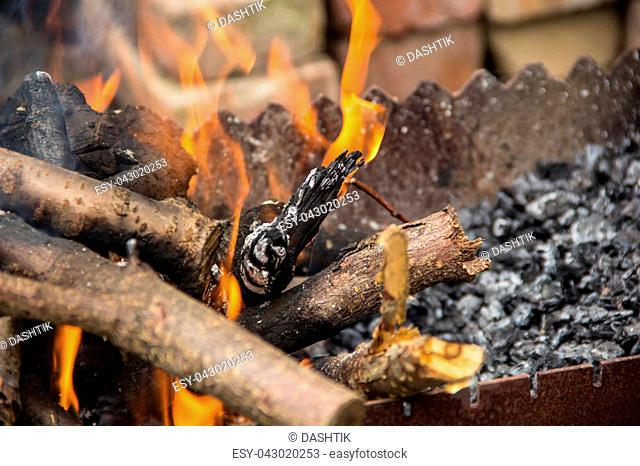 burning logs in a brazier. The flames on the background of the harvested wood