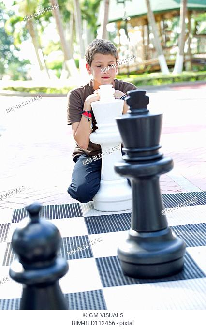 Hispanic boy playing with oversized chess set