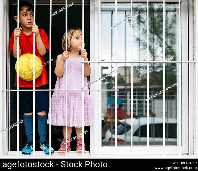 Children standing at open window at window grate