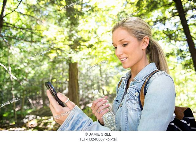 Woman using cell phone in forest