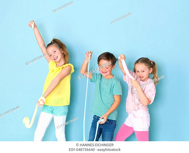 two beautiful and funny girls and one cool boy playing with a lot of slime in front of blue background and having a lot of fun in the studio