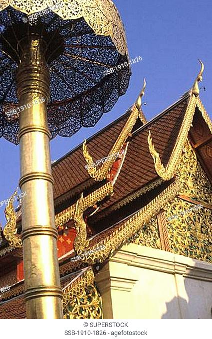 Richly decorated temple exterior with flying buttresses evident THAILAND Chang Mai