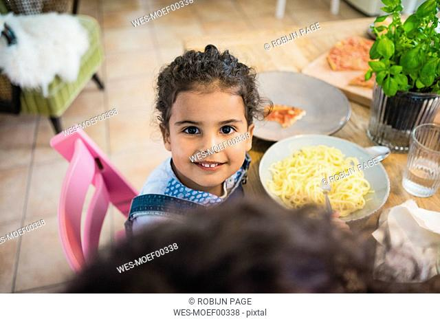 Portrait of a cheeky little girl eating spaghetti