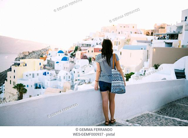 Greece, Santorini, Oia, back view of woman looking to the village at evening twilight