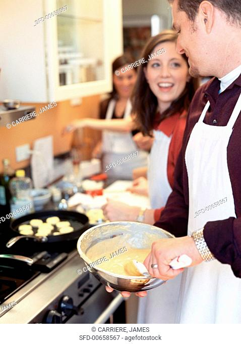 Three people cooking in a kitchen