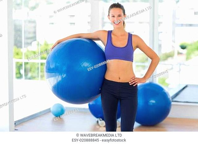Smiling fit woman holding fitness ball in gym