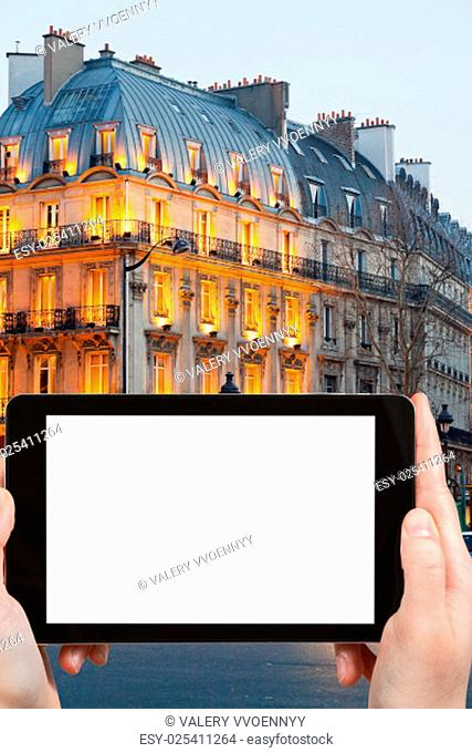 travel concept - tourist photograph house on boulevard Saint Michel in Latin Quarter in evening, Paris, France on tablet pc with cut out screen with blank place...