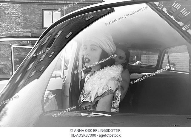 Female couple sitting in old car viewed through windscreen