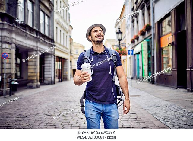 Traveler with backpack walking down city street and holding coffe
