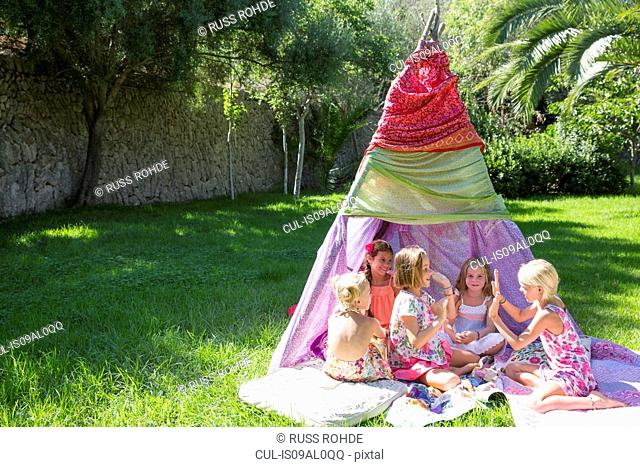 Five girls playing clapping games in front of teepee