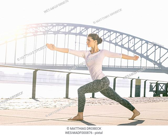 Germany, Cologne, young woman practicing yoga, warrior pose