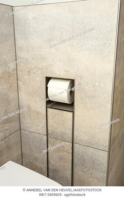 A white roll of soft toilet paper neatly hanging on a modern chrome holder in the wall close-up