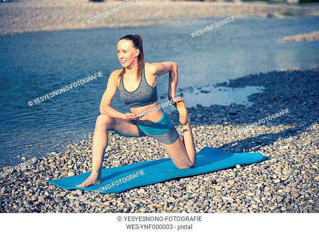 Woman practicing yoga by the riverside
