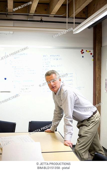 Caucasian businessman leaning on conference desk in office