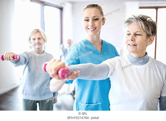 Woman holding hand weight with physiotherapist