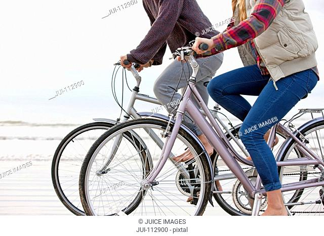 Cropped view of couple riding bicycles on beach