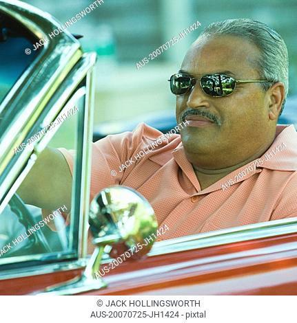 Senior man driving a convertible car