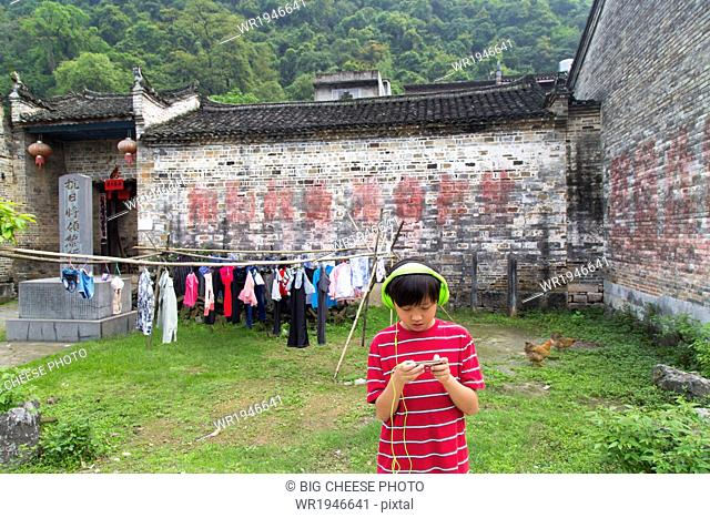 Boy wearing headphones uses an electronic device in a rural Chinese village
