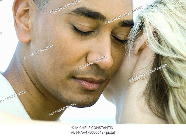 Couple cheek to cheek, man's eyes closed, close-up
